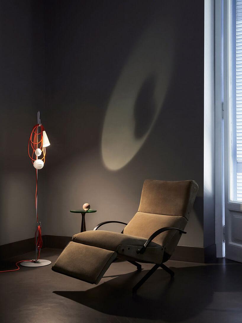 ciemne wnętrze zlampą podłogową obok rozkładanego fotela