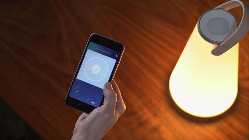 kobieta trzymająca telefon na tle lampy stołowej iblatu