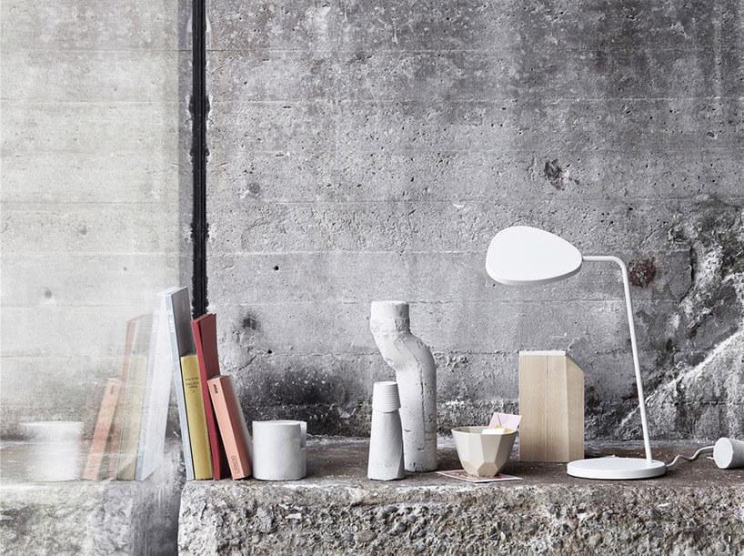 lampa stołowa na kamiennym blacie na tle betonowej ściany