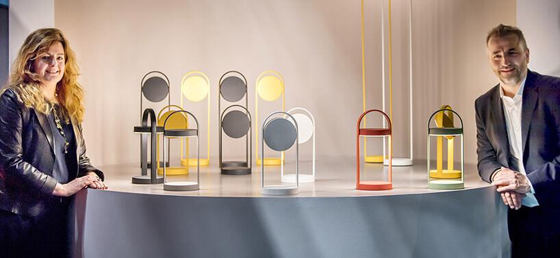 twórcy obok swoich lamp stołowych przypominających uchwyt