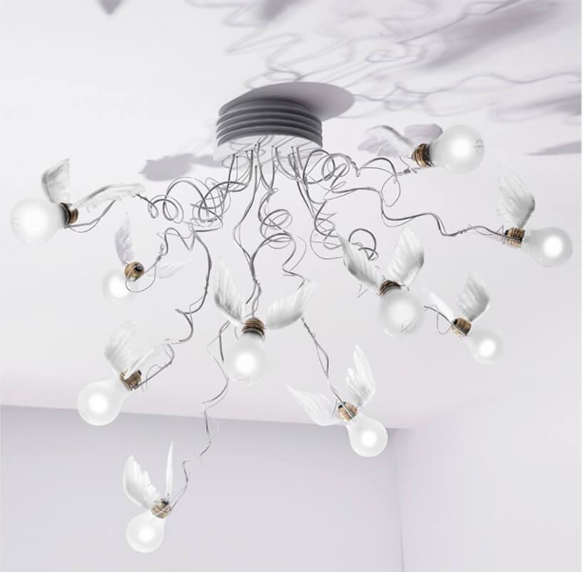 wyjątkowa biała lampa Birdie's Nest od Ingo Maurer na żarówki przyozdobione białym skrzydłami przy gwincie