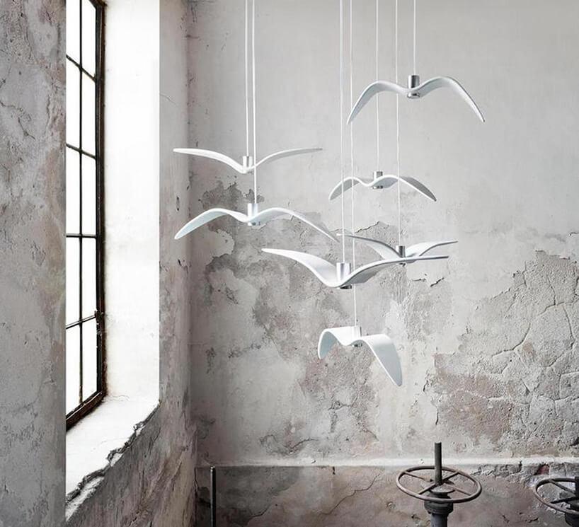 białe wiszące lampy Night Birds od Brokis wygięty metal wkształcie lecących ptaków na tle betonowej ściany