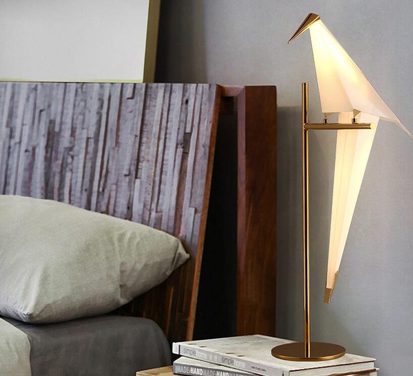 lampka stojąca Moooi wkształcie ptaka siedzącego na złotej podstawie