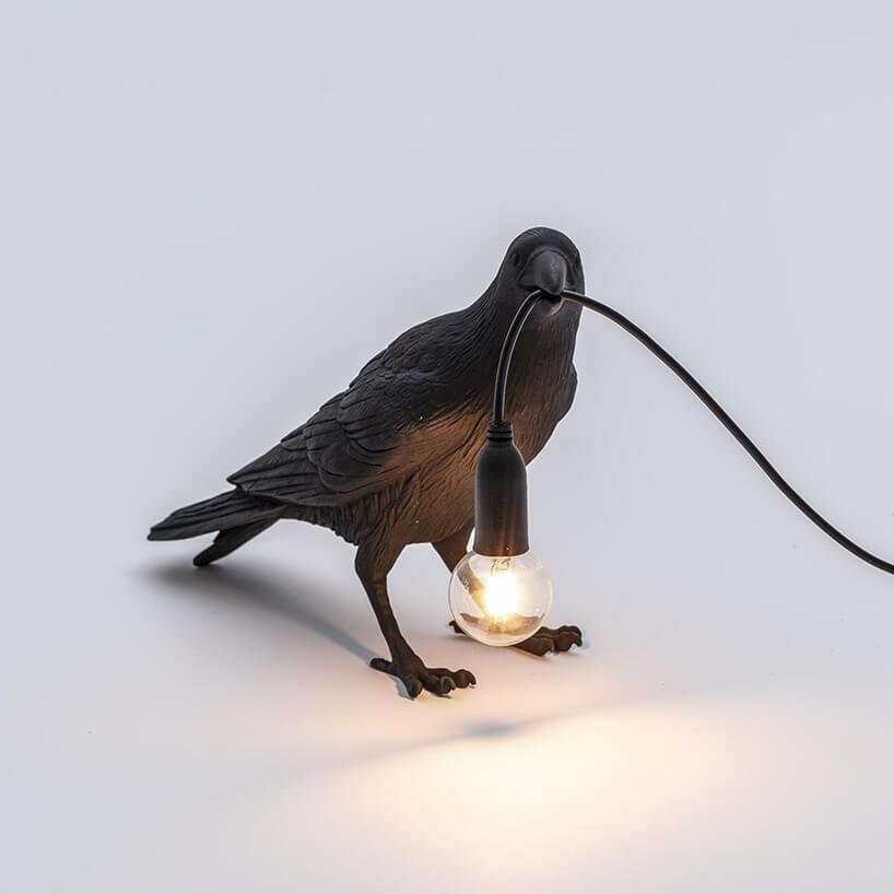 wyjątkowa czarna lampka Bird Corbeau Waiting od Seletti wkształcie kruka trzymającego kabel zodsłoniętą żarówką