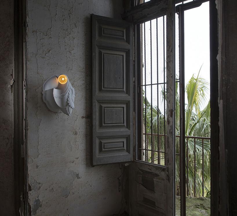 wyjątkowa szara lampa ścienna Cubano od Karman wkształcie ptaka zdużym dziobem zżarówką zamiast oka