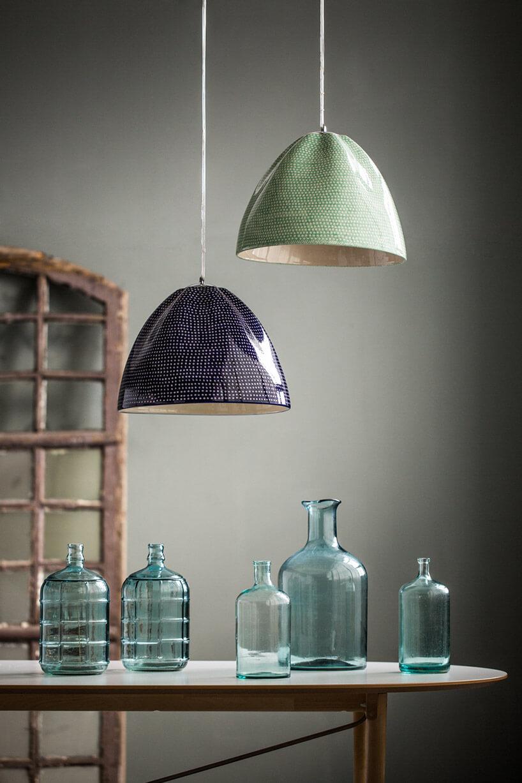 dwie wiszące lampy nad stołem zbutelkami