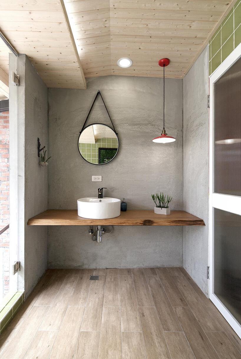 szara surowa łazienka zdrewnianym blatem zmałą umywalką pod podwieszonym czarnym okrągłym lustrem od HAO Design