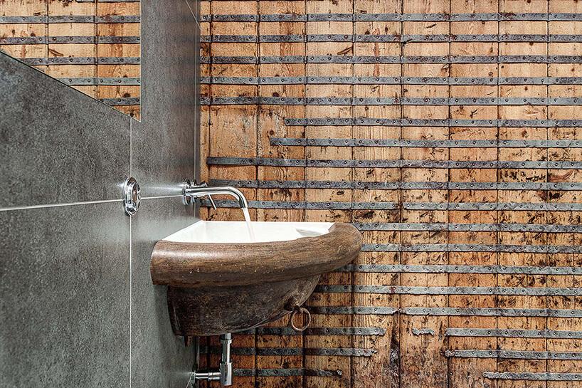 wyjątkowa łazienka znarożną umywalką na tle ściany ze starych desek ze starym metalowym wzmocnieniem od AR Design Studio