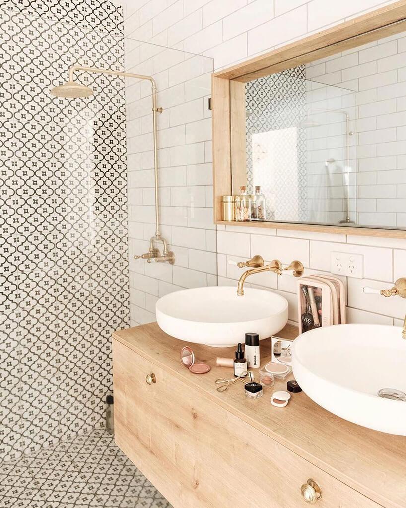 elegancka biała łazienka zbiało brązową płytką obok drewnianej podwieszanej szafki zdwoma umywalkami