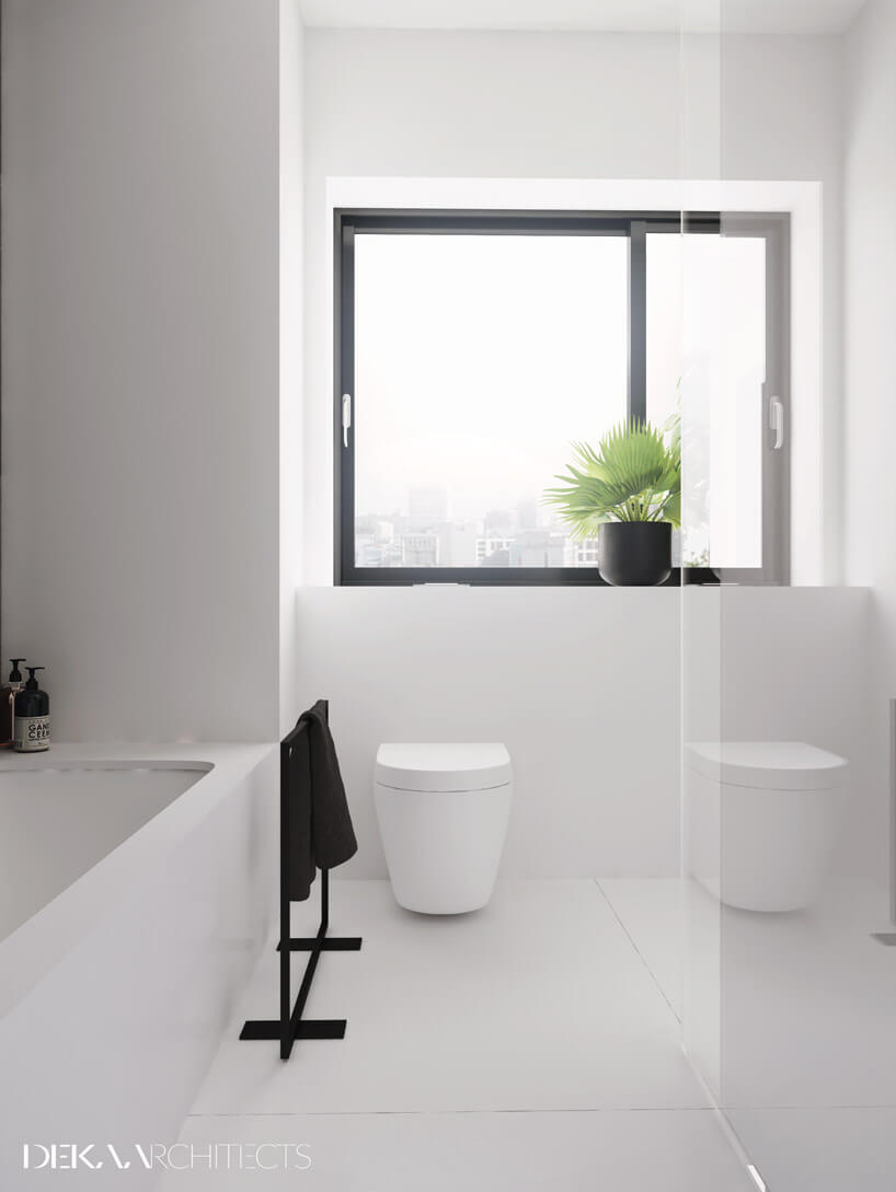 biała łazienka zczarnym stojakiem na ręcznik