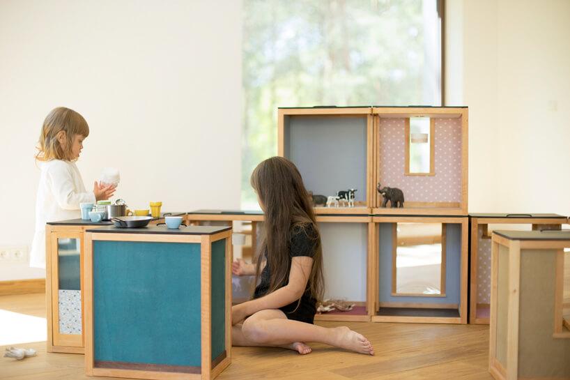 dziewczynka pomiedzy niebieskimi szafeczkami na tle beżowej ściany