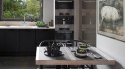 szafki kuchenne zciemnymi frontami zpopielatą podłogą przy drewnianym stole kuchennym