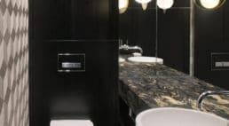 toaleta zdużym lustrem oraz wzorzystą oraz czarną ścianą