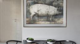 biały stół zczterema czarnymi krzesłami przy wiszącym obrazie