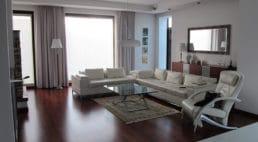duży przestronny salon zoknem wraz zdrewnianą podłogą ijasnymi meblami