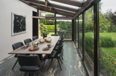 jadalnia zrobiona na zadaszonym szklanym tarasie ze szarą ścianą oraz ciemnymi materiałowymi krzesłami