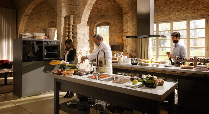 ludzie zajmujący się gotowaniem wnowoczesnej kuchni