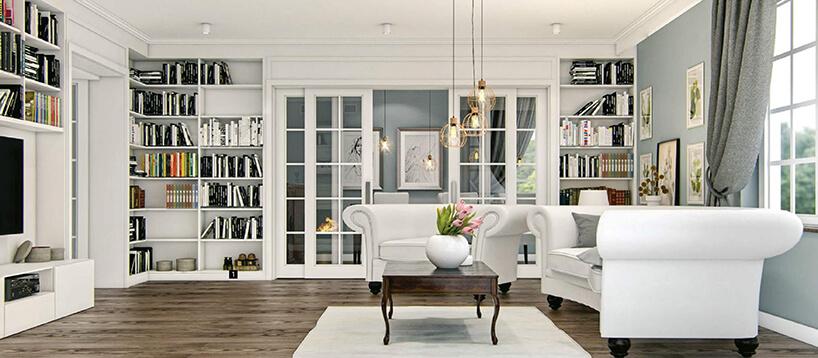 białe wnętrze zciemną drewnianą podłogą zdużą białą sofą ifotelem na krótkich drewnianych nogach