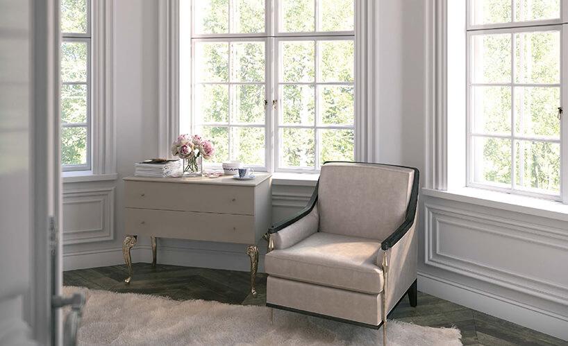 wyjątkowy beżowy fotel obok komody na wysokich złotych nogach na tle dużych białych starych okien