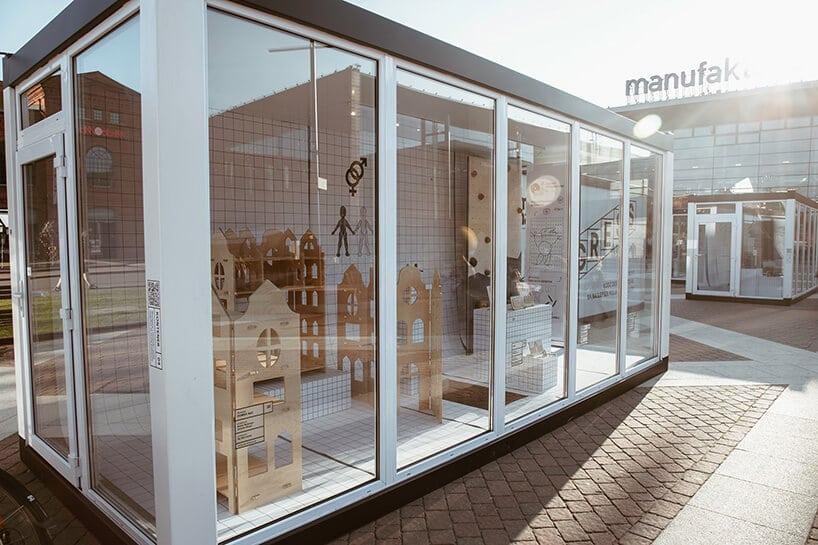 wystawa wbiałych szklanych kontenerach prac finalistów włódzkiej manufakturze