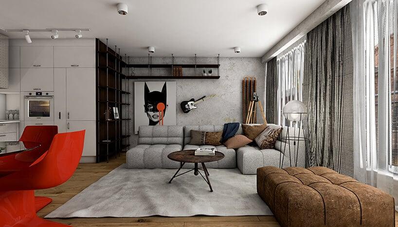 salon wmałym mieszkaniu zpuszystą szarą kanapę oraz obraz na ścianie