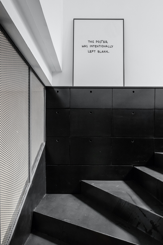 loft projektu KEMA studio czarne schodu skręcające przy czarnych szafkach pod biała ścianą