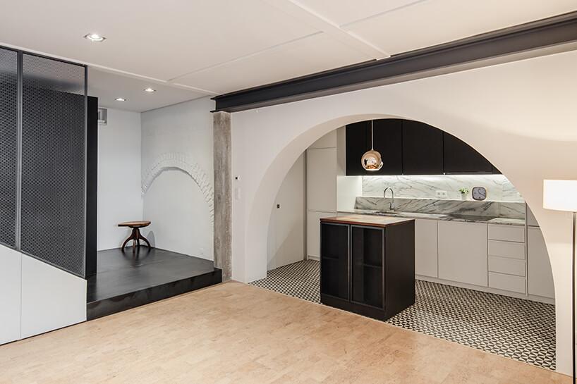 loft projektu KEMA studio biało czarna kuchnia zmałą wyspą pod łukiem wejściowym
