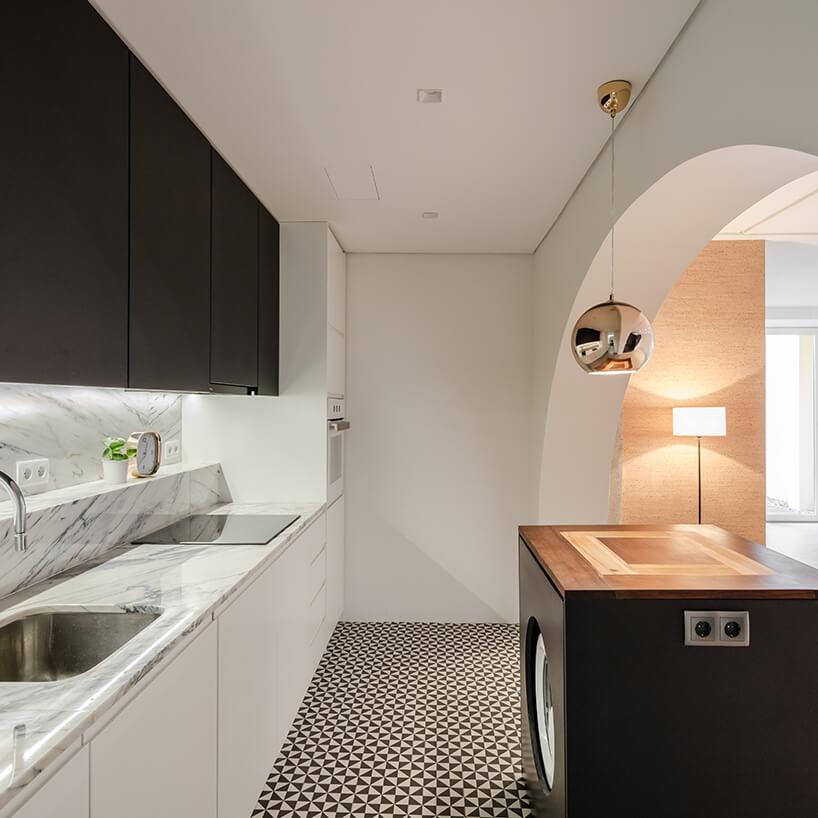 loft projektu KEMA studio biała kuchnia zkamiennym białym blatem pod czarnymi szafkami górnymi ipodłoga ibiało czarne trójkąty