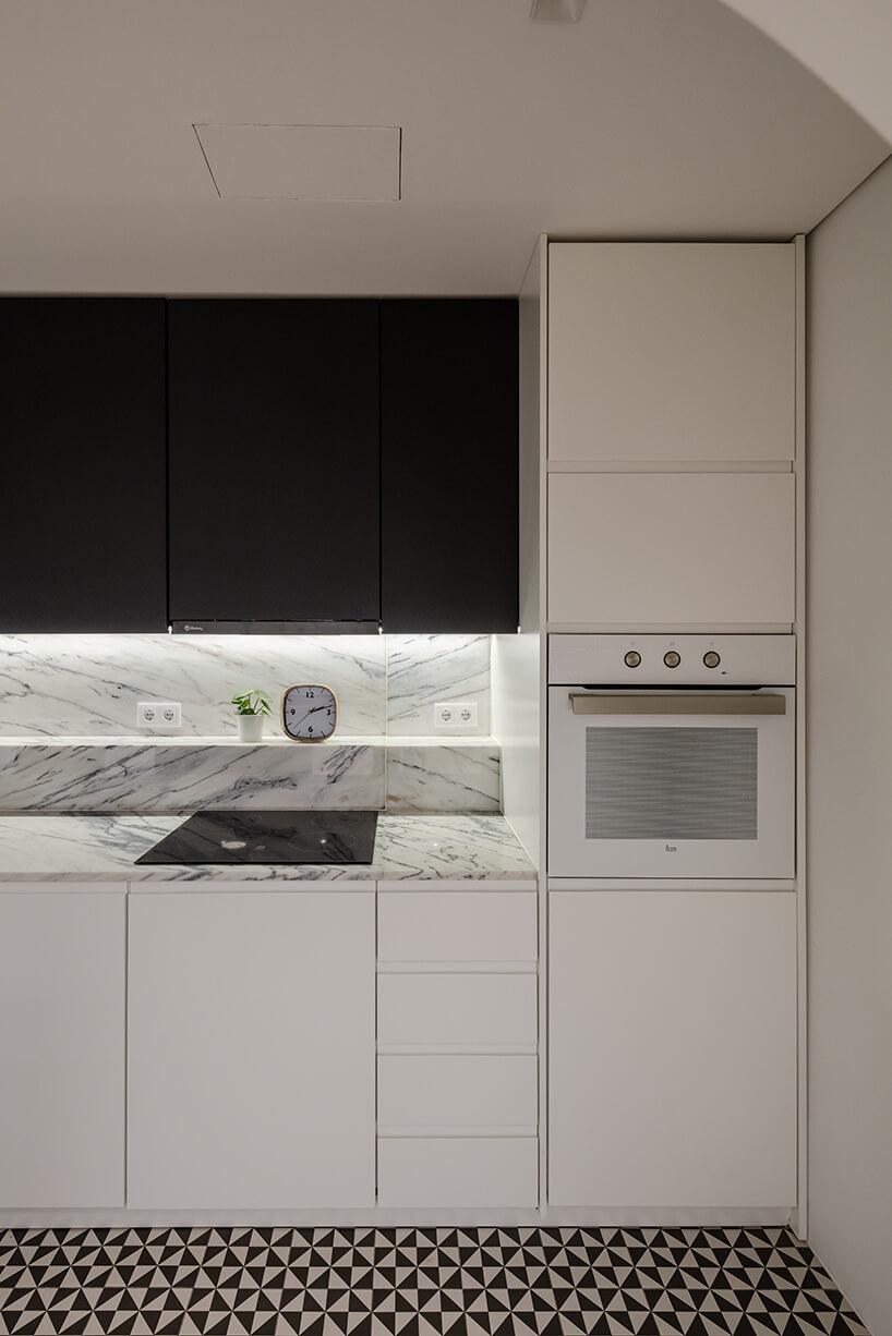 loft projektu KEMA studio biała kuchnia zbiałym kamiennym blatem ibiałym piekarnikiem