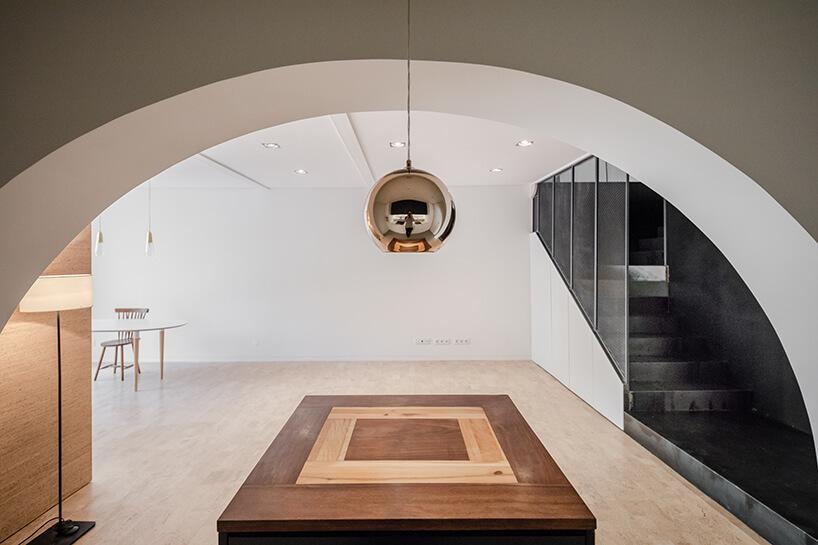 loft projektu KEMA studio drewniany niski stół pod białym łukiem wejściowym