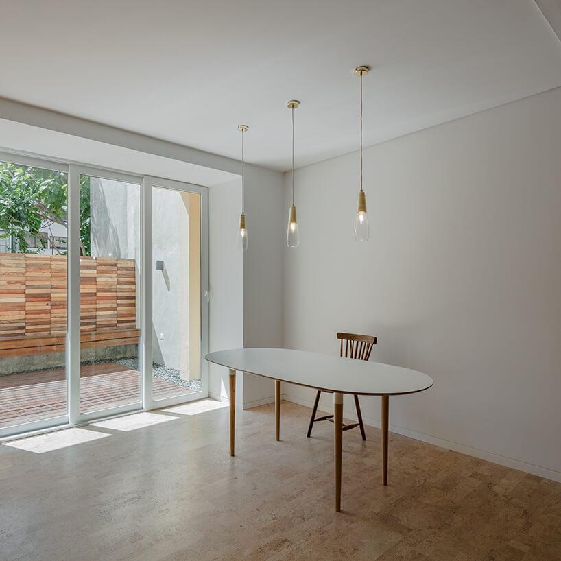 loft projektu KEMA studio biały stół na cienkich drewnianych nogach wbiałym pustym salonie