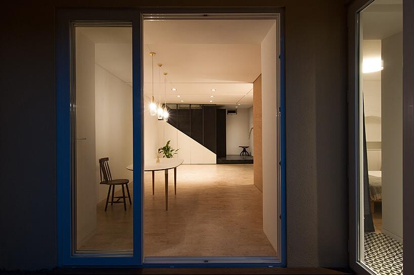 loft projektu KEMA studio jasny salon zdrewnianym stołem widziany nocą przez otwarte drzwi