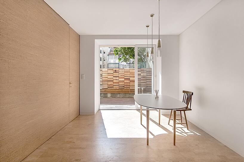 loft projektu KEMA studio białe pomieszczenie zdrewnianyms stołem na tle wyjścia tarasowego