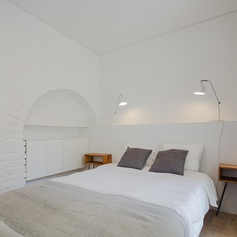 loft projektu KEMA studio biała sypialnia zdużym łóżkiem pomiędzy dwoma małymi szafkami nocnymi