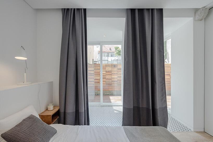 loft projektu KEMA studio biała sypialnia zszarymi zasłonami ioknem na taras zdrewnianym płotem
