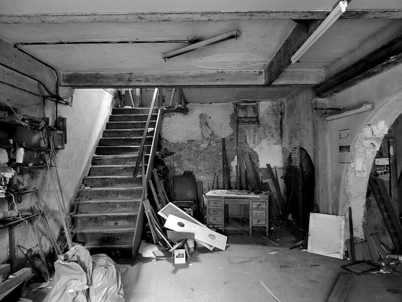 loft projektu KEMA studio obdrapane wnętrze zzdrewnianymi schodami iduża liczbą starych rzeczy