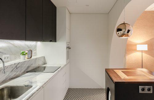 loft projektu KEMA studio biała kuchnia z kamiennym białym blatem pod czarnymi szafkami górnymi i podłoga i biało czarne trójkąty