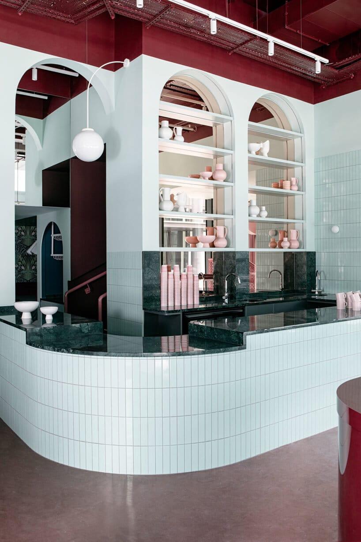 wnętrze lokalu usługowego projektu Kingston Lafferty Design czarna zaokrąglona kamienna lada wykończona małymi białymi płytkami