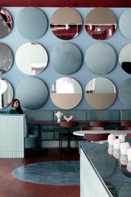 wnętrze lokalu usługowego projektu Kingston Lafferty Design niebieska ściana zokrągłymi dekoracjami na zielonym długim siedziskiem