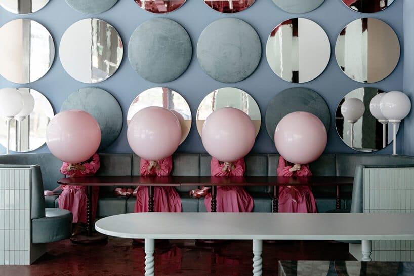 wnętrze lokalu usługowego projektu Kingston Lafferty Design niebieska ściana zokrągłymi dekoracjami na zielonym długim siedziskiem na którym siedzą cztery kobiety trzymające różowe balony