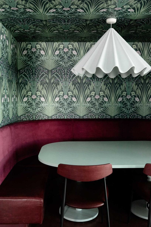 wnętrze lokalu usługowego projektu Kingston Lafferty Design zielony stolik zczerwonym siedziskiem pod białą lampą na tle ściany zzieloną roślinną tapetą