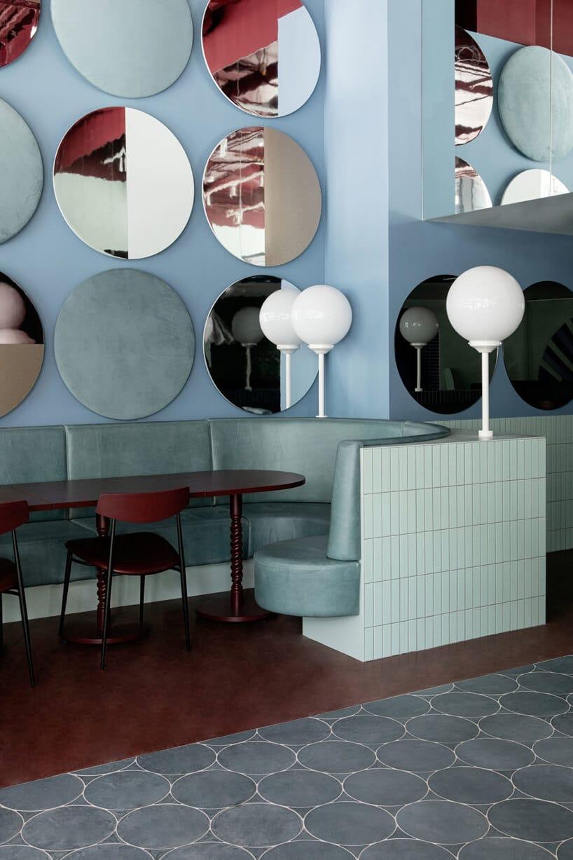 wnętrze lokalu usługowego projektu Kingston Lafferty Design ciemno brązowy stolik przy zielonym zaokrąglonym siedzisku zabudowanym białymi płytkami