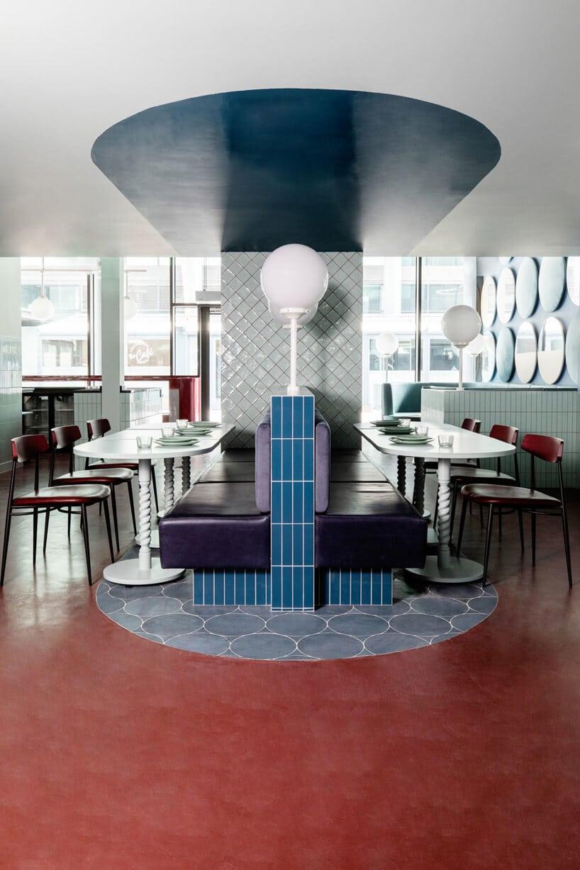 wnętrze lokalu usługowego projektu Kingston Lafferty Design niebieska ścianka oddzielająca dwa fioletowe siedziska