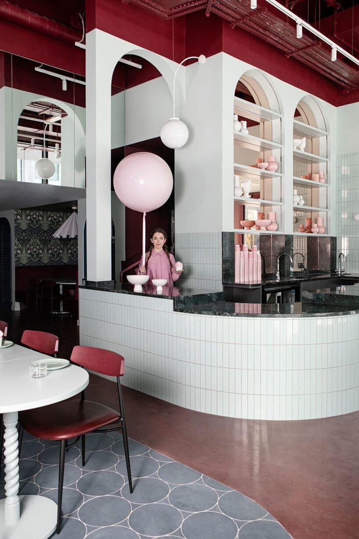 wnętrze lokalu usługowego projektu Kingston Lafferty Design kobieta trzymająca duży różowy balona za czarno białą ladą