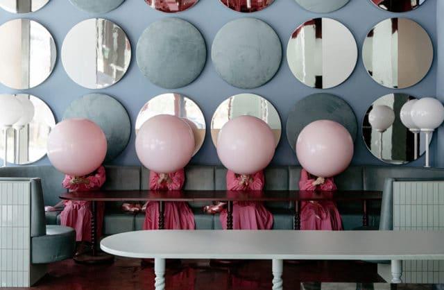 wnętrze lokalu usługowego projektu Kingston Lafferty Design niebieska ściana z okrągłymi dekoracjami na zielonym długim siedziskiem na którym siedzą cztery kobiety trzymające różowe balony