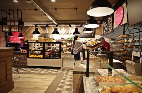 nowoczesne beżowe wnętrze piekarni, kawiarni, cukierni róża z dużym czarnym lampami wiszącymi