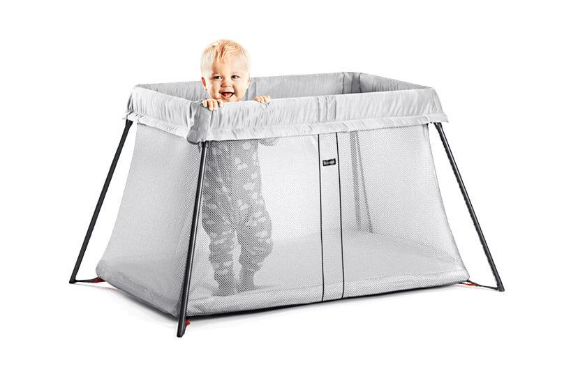 dziecko stojące wewnątrz łóżeczka turystycznego