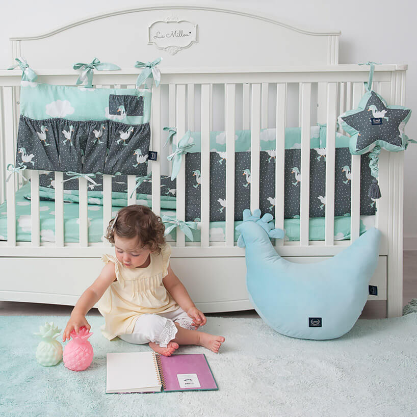mała dziewczynka bawiąca się przed łóżczekiem