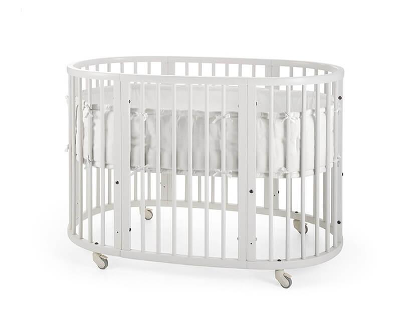 białe owalne łóżeczko dla niemowlecia