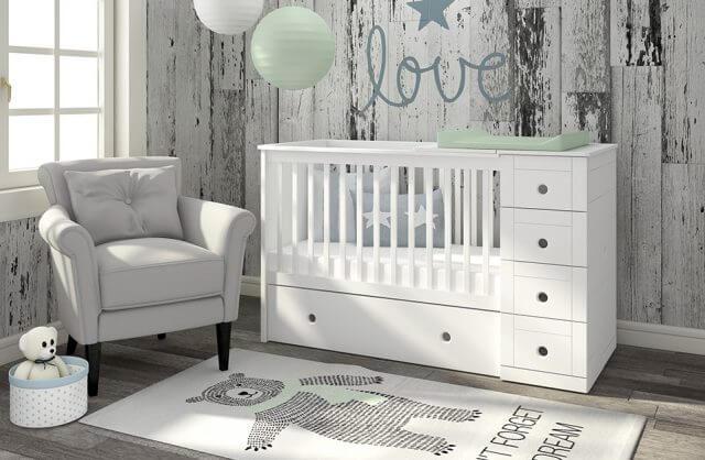 białe łóżeczko w pokoju obok szarego fotela